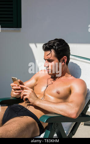 Shirtless Young Man Drying Off in Hot Sun Listening to Music Through Earphones, Muscular Man Wearing Bathing Suit Sunbathing on Beach Lounge Chair, Ey - Stock Image