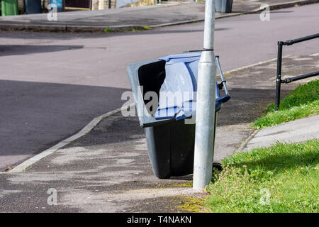 An empty blue recycling wheelie bin with a broken blue lid has been leant against a lamp post - Stock Image
