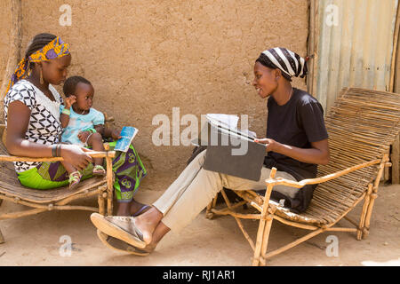 Baribsi village, Yako province, Burkina Faso; Sally Belem, 32,  conducting a survey into child nutrition interviews a teenage mother. - Stock Image