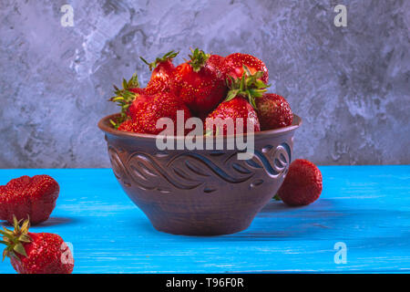 Ripe strawberries in a ceramic brown bowl on a blue background - Stock Image