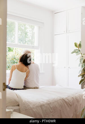 Serene senior couple sitting on bed and looking out window - Stock Image