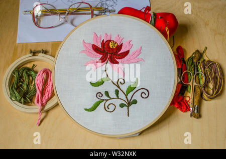 Wooden hoops with embroidered stylized red flower with lying next to the sketch with glasses, scissors, colored thread and needles on light plywood - Stock Image