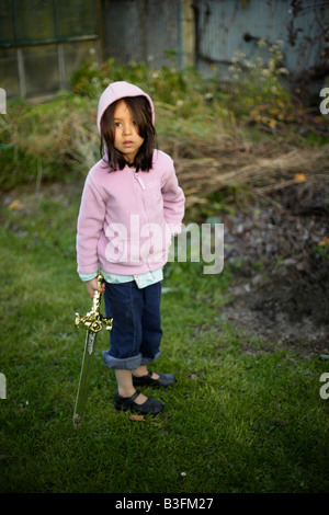 Five year old girl in evening sunlight with toy sword - Stock Image