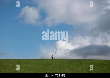 A lone woman walks through Crow Park, Keswick, Lake District, UK. - Stock Image