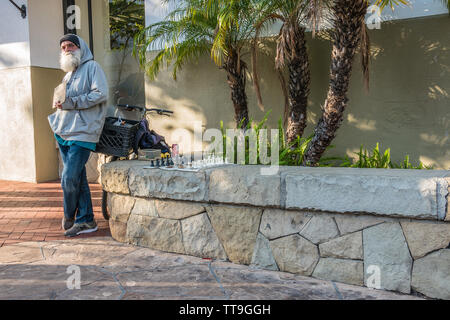 An older Caucasian male holds a sign challenging passersby to a game of chess. He has his chess board set up ready to play on a low stone wall beside - Stock Image