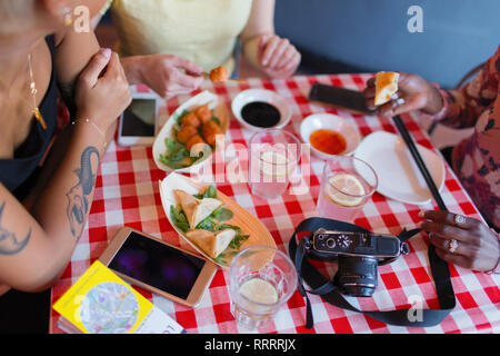 Female tourists eating at restaurant - Stock Image