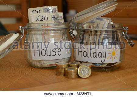 Glass savings jars with house and holiday written on white labels with currency notes inside. New pound coins stacked - Stock Image