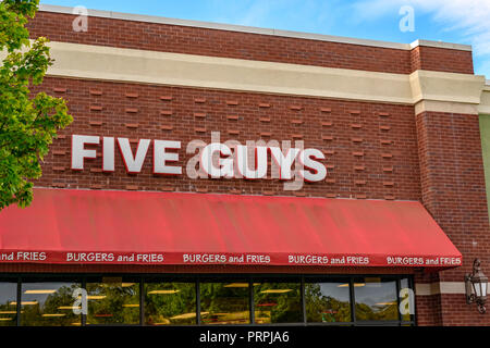 Five Guys hamburger restaurant front exterior entrance of the chain restaurant showing the corporate sign and logo in Montgomery, Alabama USA. - Stock Image