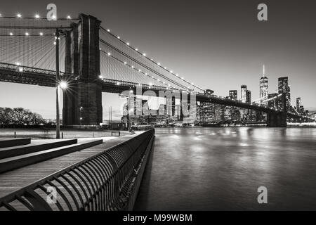 Brooklyn Bridge Park boardwalk in evening with the skyscrapers of Lower Manhattan, East River, and the Brooklyn Bridge in Black & White. New York City - Stock Image