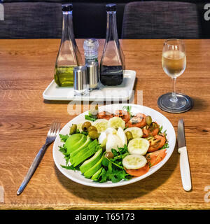 Healthy evening meal. Salad with avocado, tomato, cucumber. rocket, olives & cheese on a white dinner plate - Stock Image