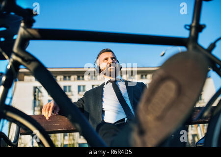 Businessman commuter with headphones and bicycle sitting on bench in city, listening to music. - Stock Image