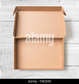 Open cardboard box top view on white wood floor - Stock Image