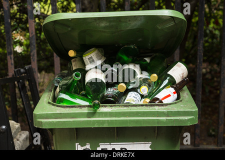 Green glass recycling bin full of bottles - Stock Image