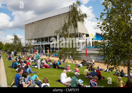 People sitting on lawns by River Lea with Aquatics Centre on a sunny day at Olympic Park, London 2012 Olympic Games - Stock Image