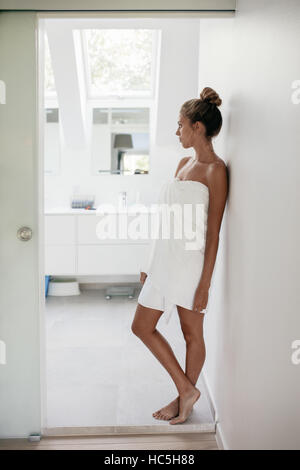 Full length shot of young woman wrapped in towel standing in bathroom looking away and thinking. Female after shower - Stock Image