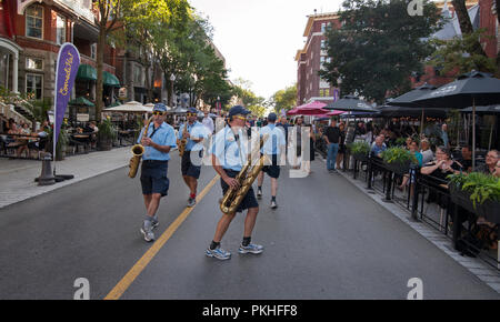 A strolling group of saxophone players entertain restaurant patrons on the Grande Allée during a summer street festival in Québec City, Canada. - Stock Image