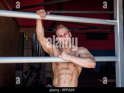 Muscular shirtless young man standing in gym - Stock Image