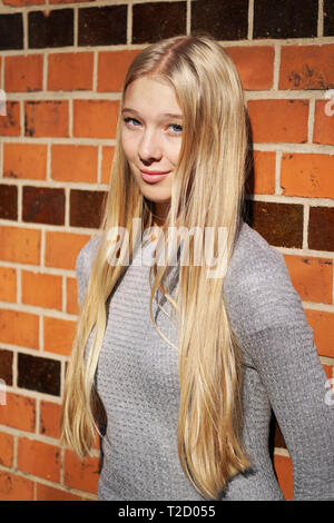 teenage girl with long blond hair leaning against brick wall - Stock Image