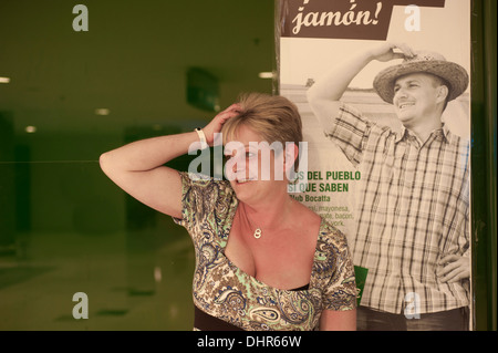 woman imitating bill poster with hand on head - Stock Image