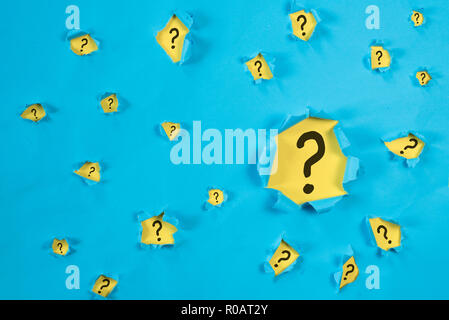 Torn blue paper revealing QUESTION MARK on yellow paper. concept of questions, faq, q&a, problem, riddle and quiz background - Stock Image