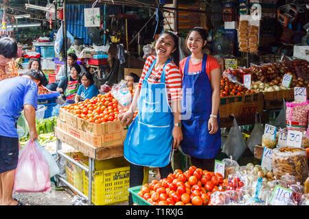 Bangkok, Thailand - 11th March 2017: Girls laughing on vegtable stall. Pak Khlong Talat is citys biggest wet market - Stock Image
