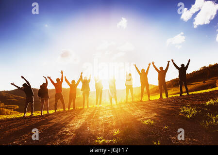 Big group of friends raising arms on sunset together - Stock Image