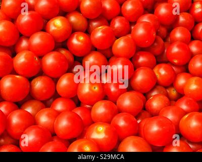 A pile of Cherry Tomatoes. The tomato is consider both a fruit and a vegetable, depending on its classification. Photo Credit - © COLIN HOSKINS. - Stock Image