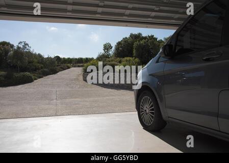 Car in garage leading toward driveway - Stock Image