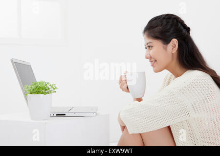 Young woman holding a coffee cup and looking at the laptop with smile, - Stock Image