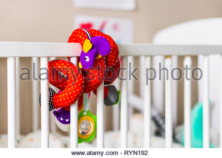 Poznan, Poland - November 18, 2018: Colorful toy snake attached on a wooden baby bed in a child room. - Stock Image