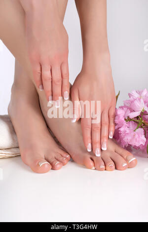 Woman legs with bare feet and hands with french manicure and pedicure on white towel in spa salon and decorative pink flower in background - Stock Image