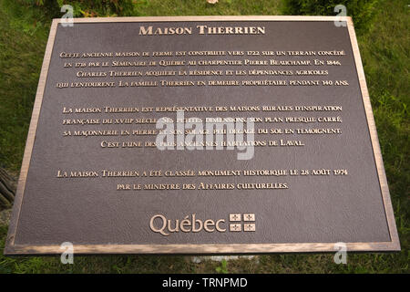 Close-up of a bronze metal historical information plaque in front of an Old 1722 Canadiana cottage style home called Maison Therrien - Stock Image