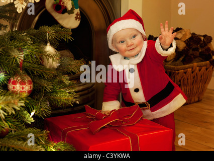 A baby santa standing next to a present - Stock Image