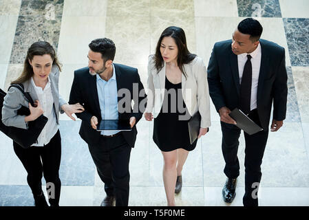 Business people walking in hotel lobby - Stock Image