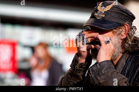 'Fast Eddie' Lafferty is the harmonica playing busker and well known face on the streets of Dundee, UK. - Stock Image