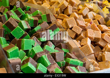 Selection of fudges for sale in a grocery stores pick n mix counter, where people buy there favourite sweets chosen - Stock Image