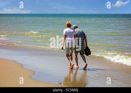 Elderly couple paddling in shallow sea water on sandy beach along the coast in summer - Stock Image