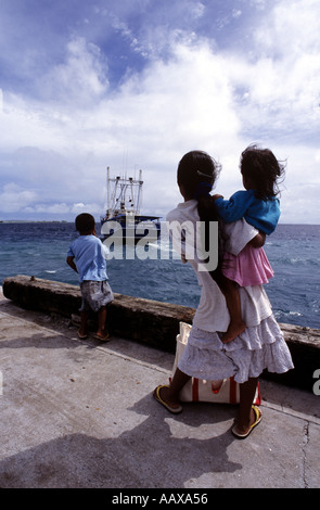 Marshall Islands Kids on the outer island of Jaluit waving off the weekly supply boat - Stock Image