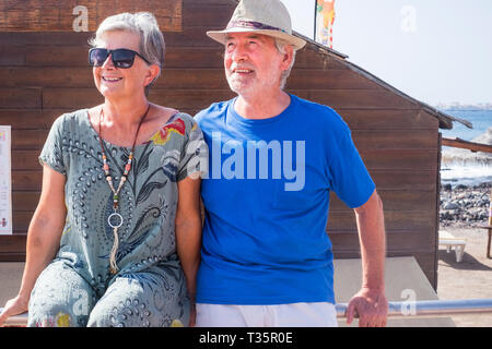 Senior couple in summer holday vacation together enjoying the outdoor leisure activity looking at the sun - together forever life for aged man and wom - Stock Image