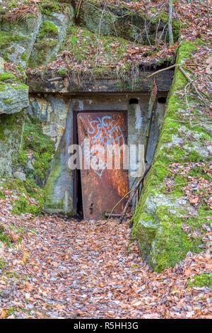 FLODA, SWEDEN - NOVEMBER 21 2018: Heavy metal door covered in graffiti slightly ajar leading into 1940s bomb shelter built into hill side - Stock Image