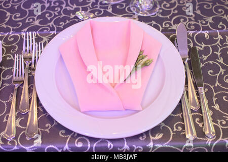 Formal table setting with silverware placed in the order of use, and elegantly wrapped napkin in the shape of a jacket on top of white china - Stock Image