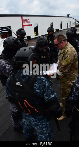 180903-N-QV906-0211 AT SEA (September 3, 2018) U.S. Coast Guard Chief Maritime Enforcement Specialist Daniel Brooks briefs a team of Philippine Coast Guardsmen at the conclusion of a practical Visit, Board, Search, and Seizure training scenario training as part of Southeast Asia Cooperation and Training (SEACAT) 2018. This is the 17th annual SEACAT exercise and includes participants from the U.S., Brunei, Bangladesh, Thailand, Philippines, Singapore, Vietnam, Malaysia and Indonesia. (U.S. photo by Mass Communication Specialist 1st Class Micah Blechner/RELEASED) - Stock Image