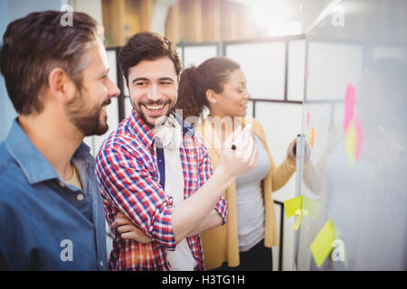 Happy executive with colleagues standing by whiteboard at creative office - Stock Image
