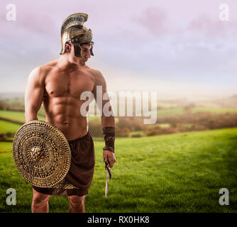 Young muscular man posing in gladiator costume - Stock Image