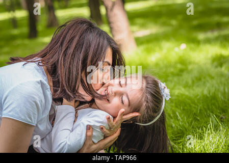 Young mom hugs and kisses her daughter showing love and support, caring young mother embrace girl.Happy mother hugging her daughter with love and natu - Stock Image