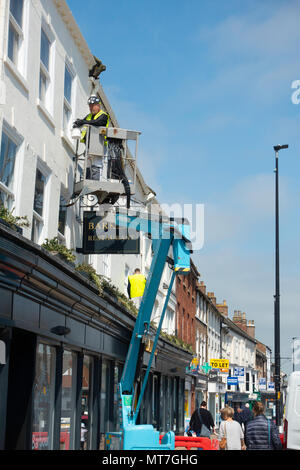 Painter decorators using an hydraulic access platform for painting the exterior of a department store - Stock Image