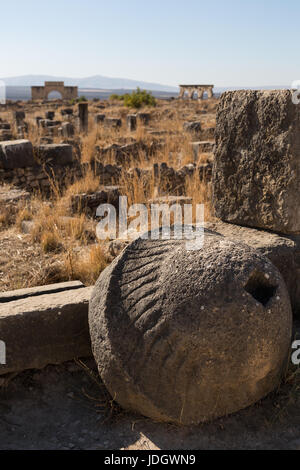 A large carved stone, possibly part of a mill, lies against a wall in the ruined Roman rown of Volubilis in Morocco - Stock Image