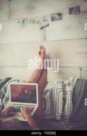 woman with nude legs lay down reverse on the couch working at laptop computer - wall wooden background with pictures - vintage cold colors filter - Stock Image