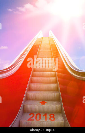 Ascending on an escalator with an arrow and 2018 written on it into sunlight. Concept photo for a successful new - Stock Image
