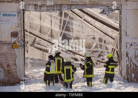 Homburg, Germany. 20th Mar, 2019. Firefighters extinguish last sources of fire after a fire in a warehouse of a plastics manufacturer. The building and surrounding area are covered with extinguishing foam. Credit: Oliver Dietze/dpa/Alamy Live News - Stock Image
